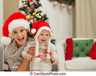 Portrait of mom and eat smeared baby girl in Christmas hats...