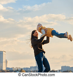 portrait of mom with a daughter in her arms against the backdrop of the cityscape