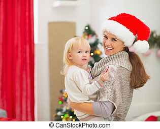 Portrait of mother and baby near Christmas tree