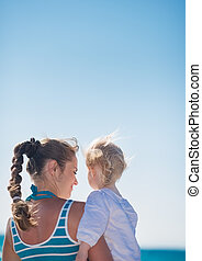 Portrait of mother and baby on beach. Rear view