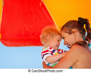 Portrait of mother and baby on beach under umbrella