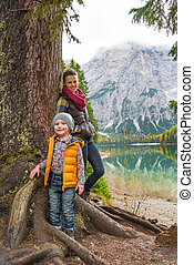 Portrait of mother and baby standing near tree on lake braies in