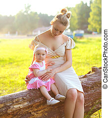 Portrait of mother and baby walking on the nature in sunny summer evening