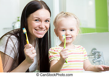 Portrait of mother and child daughter brushing teeth in the bathroom