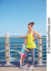 Portrait of mother and child in fitness outfit on embankment