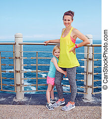 Portrait of mother and child in fitness outfit on embankment...