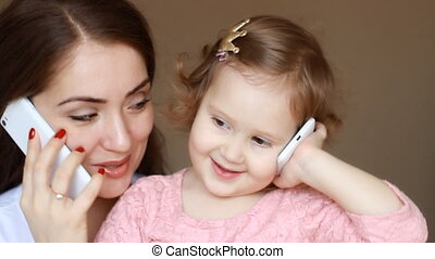 Portrait of mother and child with phones in hands close-up. Mom and her little daughter are playing and talking on smartphones