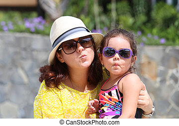 Portrait of mother and daughter giving a kiss to the camera. Foc