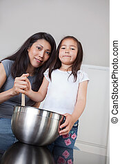Portrait of mother and daughter in kitchen