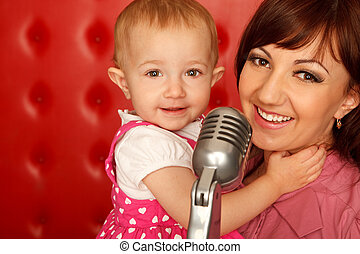 Portrait of mother and doughter with microphone on rack against red wall. Horizontal format. Close up.