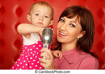 Portrait of mother and doughter with microphone on rack against red wall. Horizontal format.