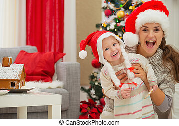 Portrait of mother and eat smeared baby in Christmas hats...