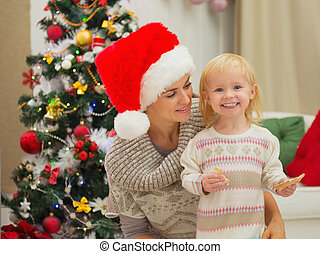 Portrait of mother and happy eat smeared baby near Christmas tree