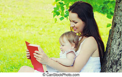 Portrait of mother and little girl baby reading a book together on the grass in a summer park