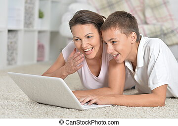 Portrait of mother and son using laptop