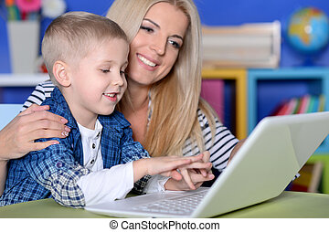 Portrait of mother and son using modern laptop