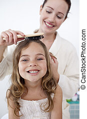 Portrait of mother doing her daughter\'s hair
