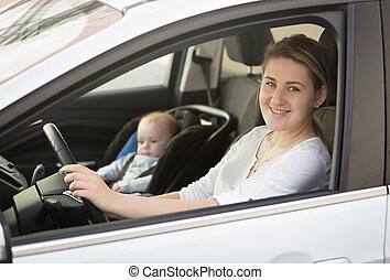 Portrait of mother driving car with little baby boy sitting in safety seat