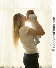Portrait of mother holding her little baby at window
