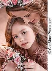 portrait of mother in flowers wreath with daughter