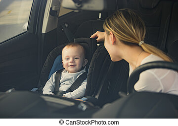 Portrait of mother looking at baby sitting on car front seat