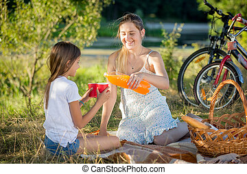 Portrait of mother pouring juice from bottle into daughter's cup on picnic at park