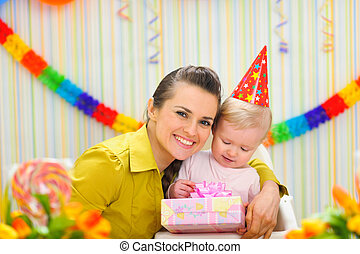 Portrait of mother with baby celebrating first birthday