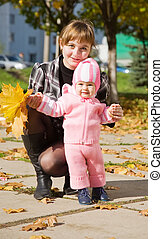 mother with her baby in autumn park
