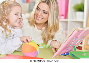 mother with little daughter reading book