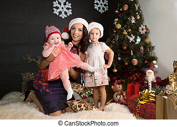 Portrait of mother with two daughters in a Christmas settings