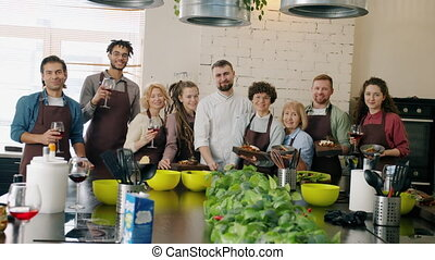 Portrait of multi-ethnic group of people standingin cooking ...