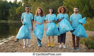 Portrait of multi-ethnic group of volunteers with bin bags ...