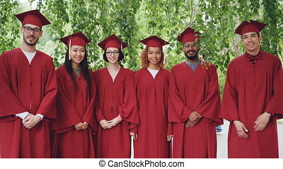 Portrait of multiethnic group of graduating students standing outdoors wearing red gowns and mortar-boards, smiling and looking at camera.