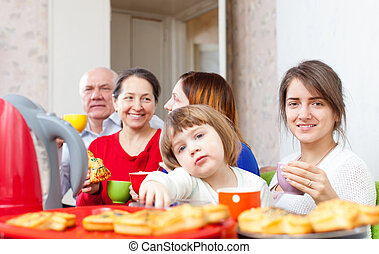 family posing together over tea at home