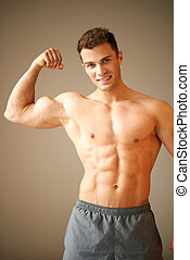 Portrait of muscular sporty man, he shows his biceps