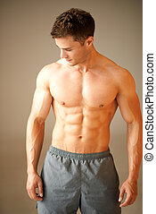 Portrait of muscular sporty man standing on brown