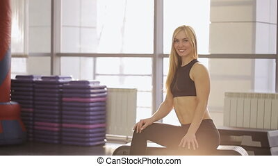 Portrait of Muscular woman athlete at the gym with a beautiful attractive fitness appearance with relaxed arms and abdominals at the gym. Healthy lifestyle well being wellness happiness concept.
