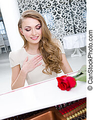 Portrait of musician with red rose playing piano