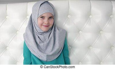 Portrait of muslim teen girl in grey hijab is looking in...
