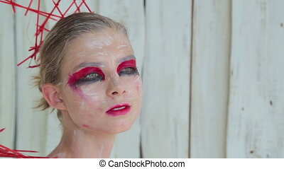 Portrait of mysterious girl with creative make-up and elegant hairstyle