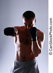 Portrait of naked sportsman boxing with his hands wrapped...