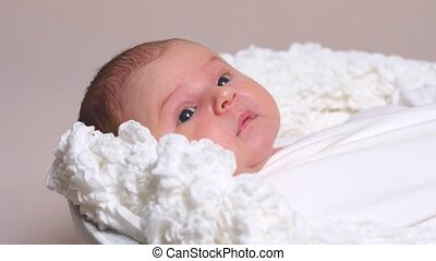 Portrait of newborn baby on white blanket