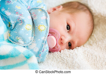 portrait of newborn baby with soother on white bedsheet