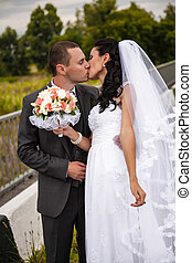 Portrait of newly married couple kissing while standing on road