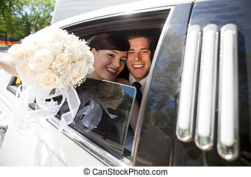 Portrait Of Newlywed Couple Smiling Sitting In Limousine...