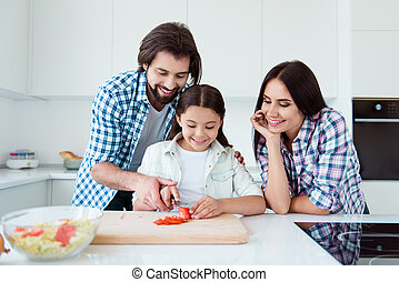 Portrait of nice cute lovely attractive charming cheerful cheery people mom dad helping pre-teen kid making fresh salad on board in light white interior room