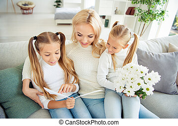 Portrait of nice lovely sweet pretty charming attractive stylish mom pre-teen girls sitting on divan giving receiving gifts daydream congrats reading post card in light white room