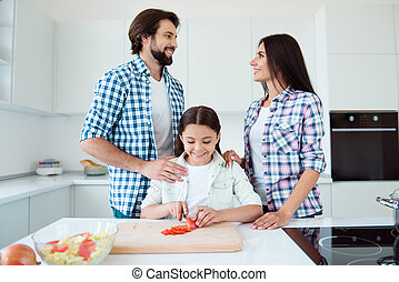 Portrait of nice lovely tender sweet attractive cheerful cheery kind people mom dad helping pre-teen kid making fresh salad dish on board in light white interior room