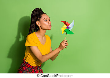 Portrait of nice pretty funny girl blowing paper propeller mill isolated over bright green color background.