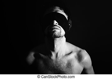 Portrait of nude young men blindfolded on a black background